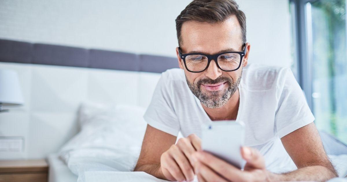 Homem deitado olhando no celular - problemas de ereção