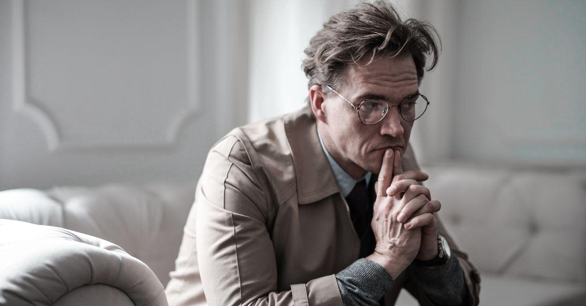homem pensativo sentado em um sofá - dúvidas dos homens no urologista